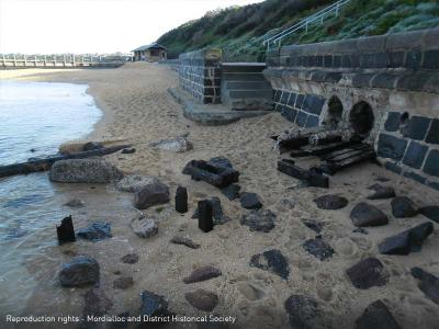 Mentone Beach showing remains of wooden rails protruding from beach wall [picture].