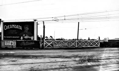 Moorabbin railway gates on Point Nepean Road. Advertisment for Creamota and Pelaco Shirts in background [picture].