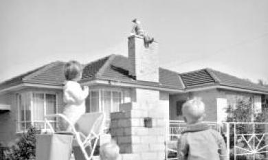 Father Christmas on the chimney of a house [picture].
