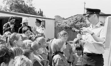 Primary school children listen to fireman talk [picture].