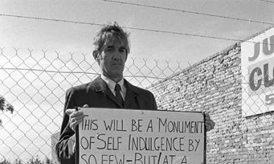 Cr Salter standing with a protest placard [picture].