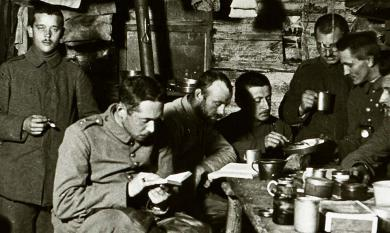 Erwin reading book in foreground, in living quarters with other soldiers, 1917