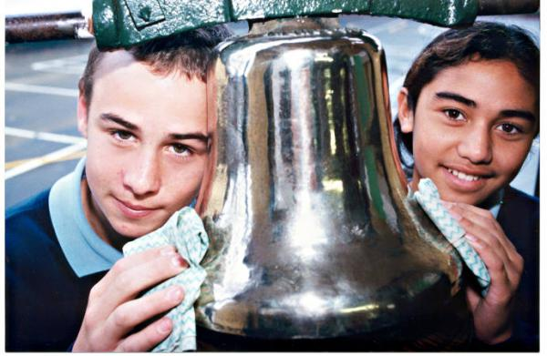 Grade 6 pupils Pat O'Neill and Jean Hetaraka polishing the school's historic bell at Heatherton Primary School [picture].